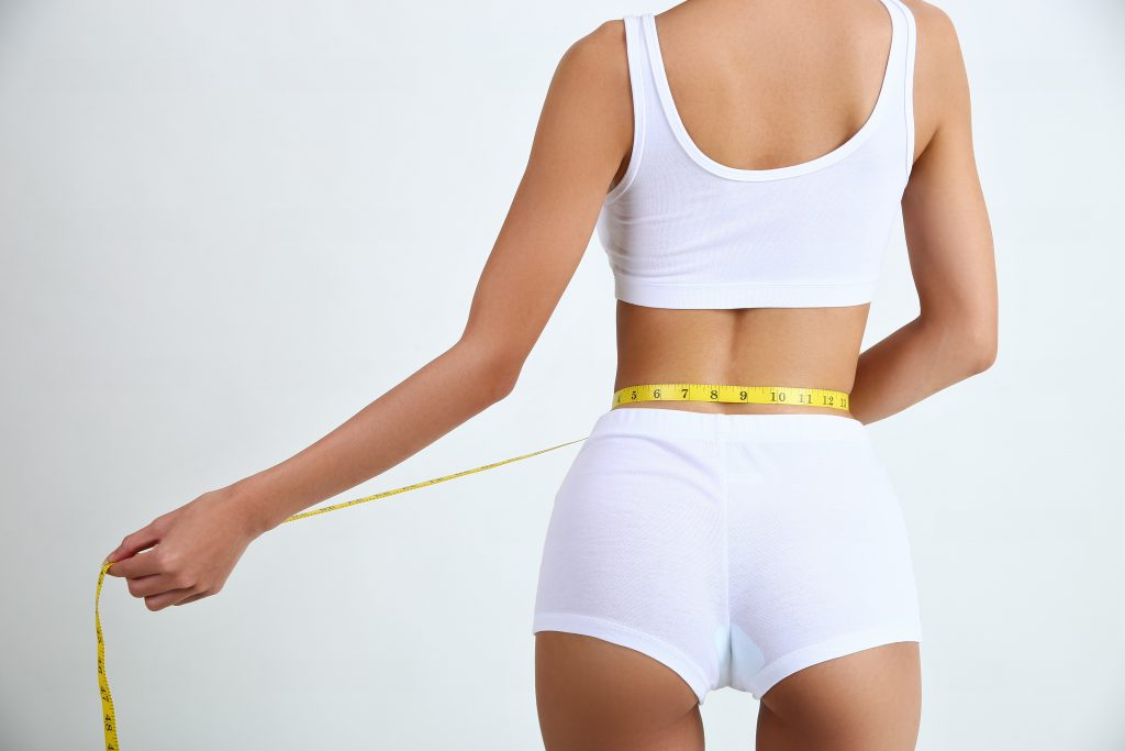 Young woman with beautiful body and measure tape